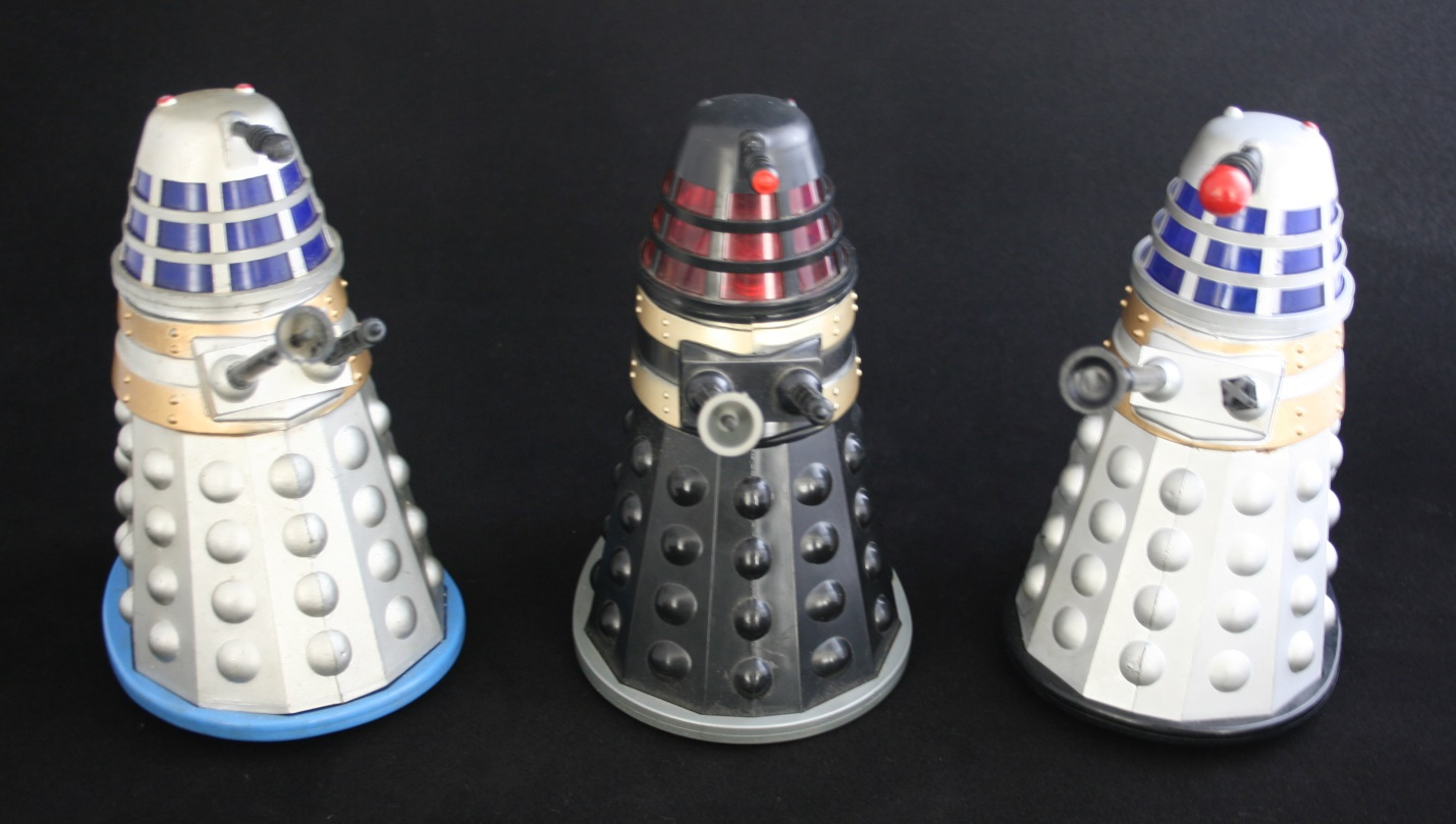 Louis Marx and Company Ltd. Later versions of the battery-operated Dalek: grey with blue base; black with grey base; and grey with black base.