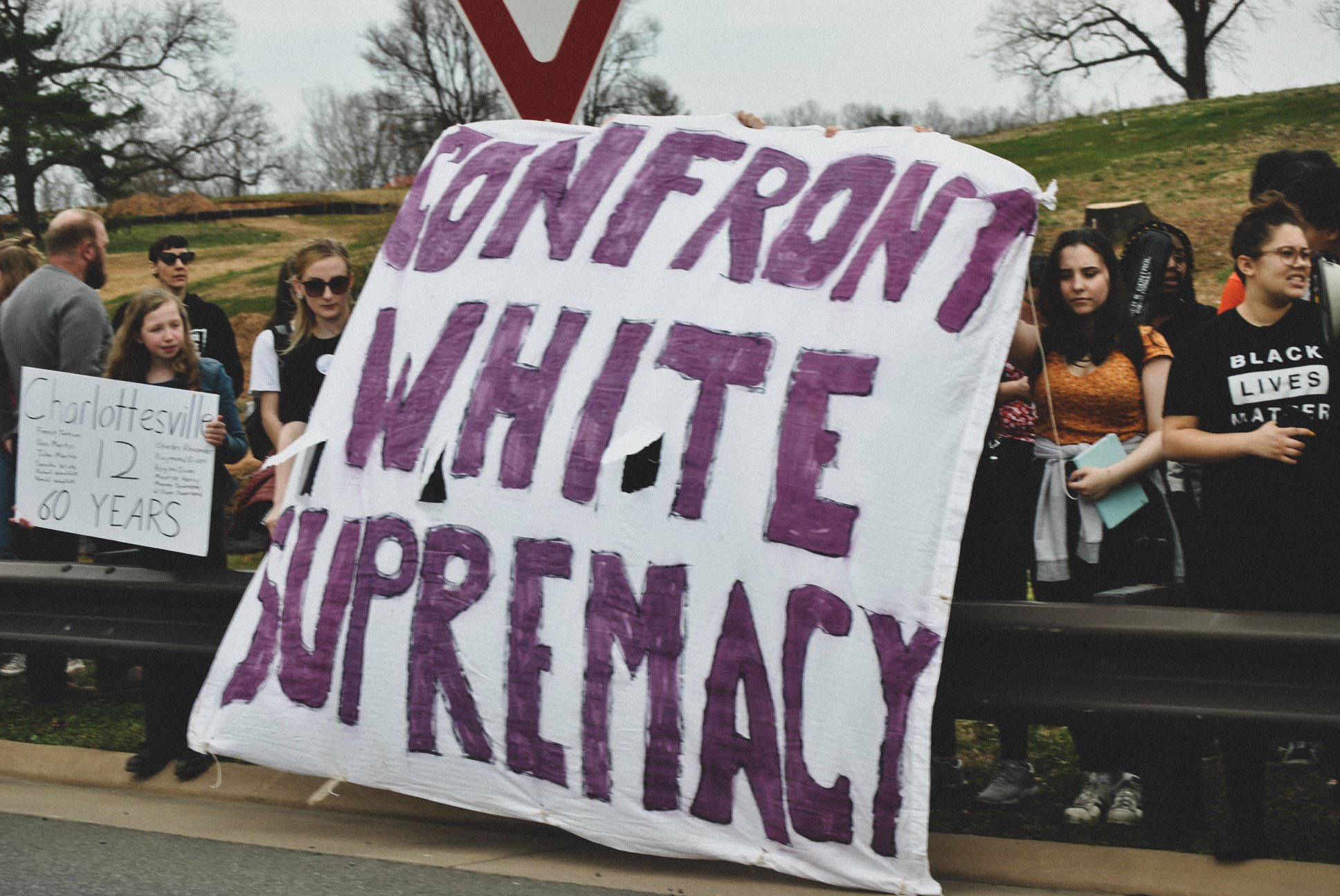 "Walkout participants stand at the edge of McIntire park holding sign onto 250 bypass that reads ""Confront White Supremacy,"" 2019. (Photo by Locs Image Photography)"