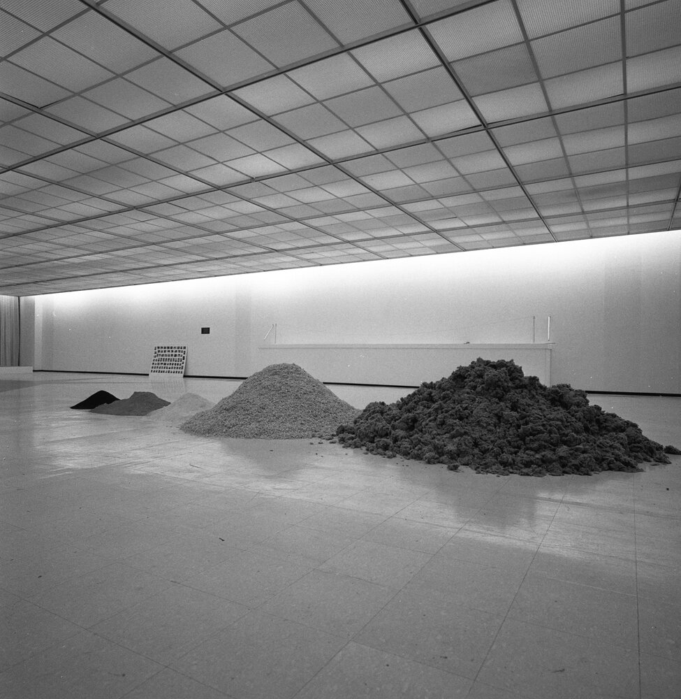 Dennis Oppenheim,  Decomposed MOCA , 1969. Building construction materials. Five piles of raw materials, ingredients of the building, distributed on the floor in piles equal to the artist's body weight. Each week the museum contacts the artist by telephone. Piles of insulation, sawdust, gypsum, cement, and metal filings then adjusted according to his exact weight reported at the time of the call. Installation at the Museum of Contemporary Art, Chicago, 1969.