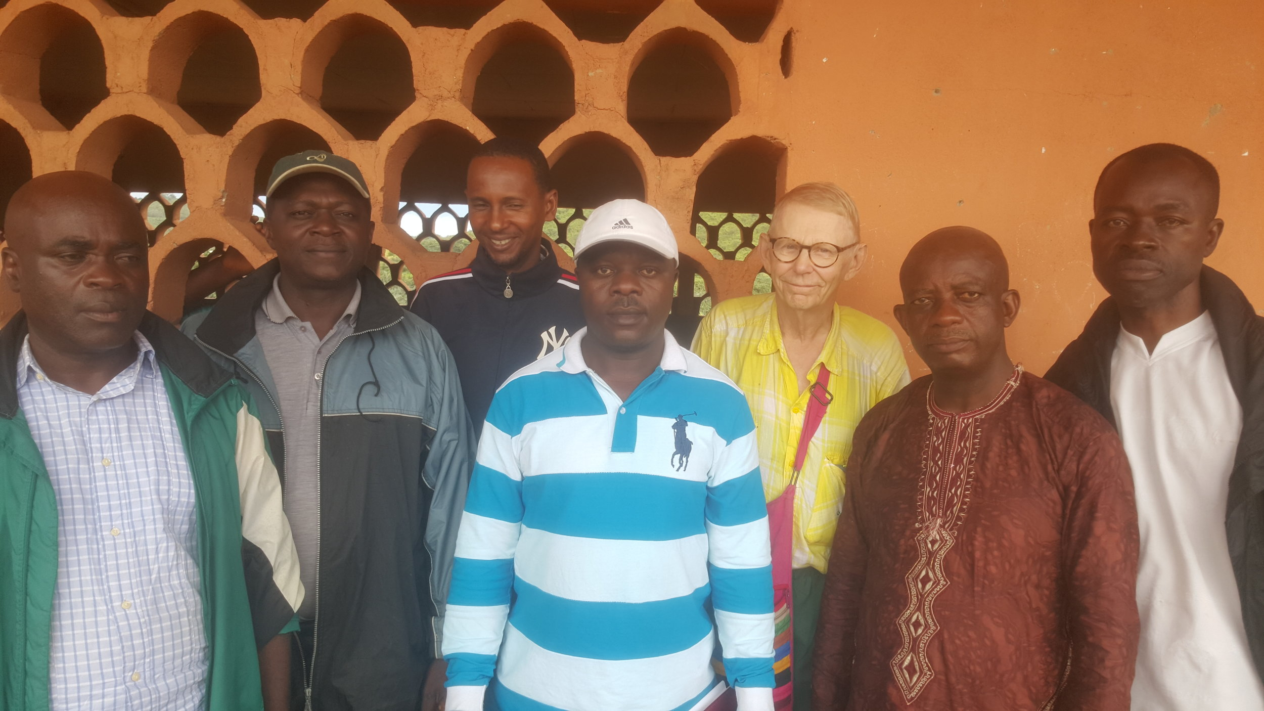 Bill Cook, of the Bill Cook foundation standing with ScholarShop's program manager (Back Row) and other community members of Upkwa. The Bill Cook Foundation donated to provide a solar panel and electricity for the Health Center in charge of Upkwa and its 4 surrounding villages.