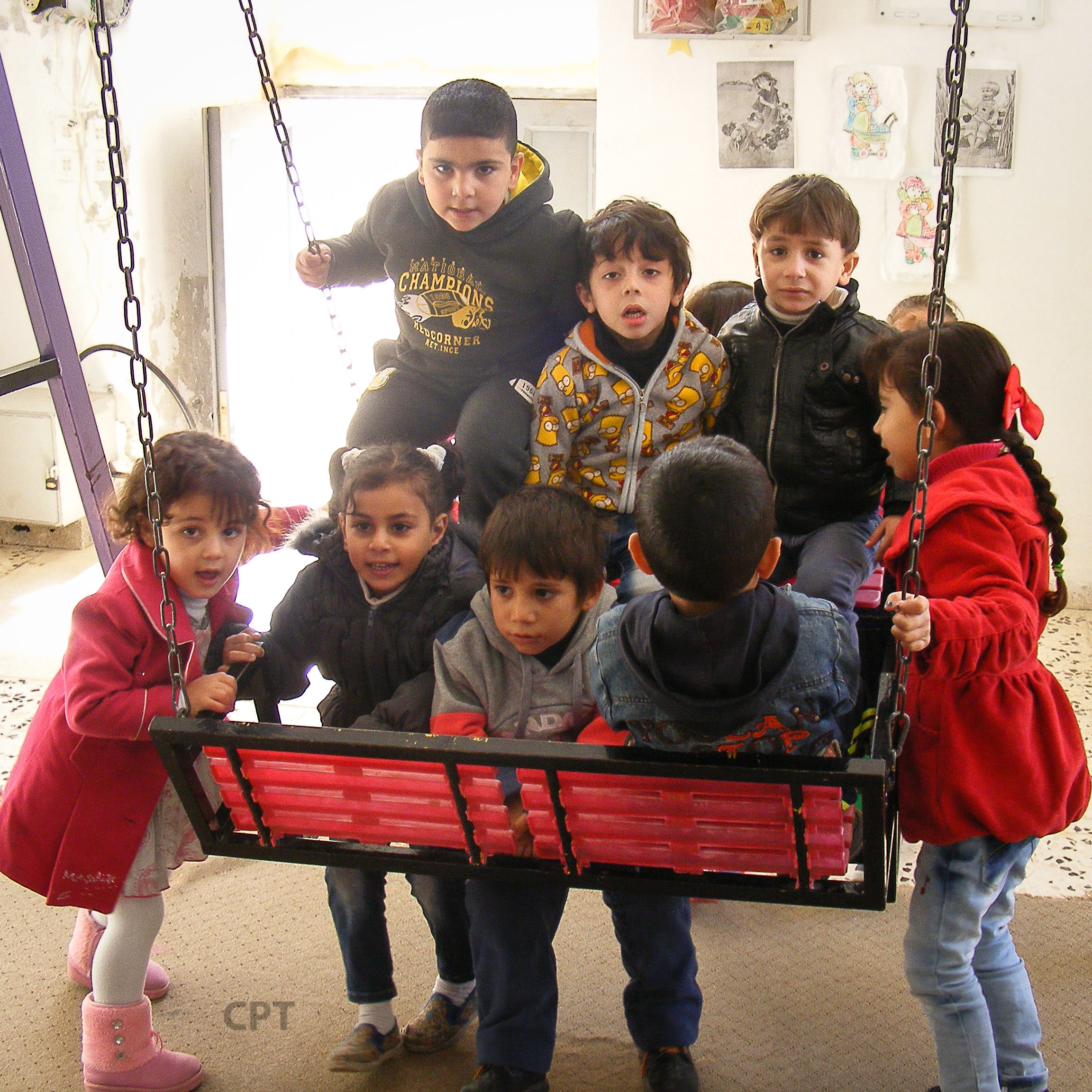 Kindergarten children play on the indoor swing, since there isn't a safe space for it outside.