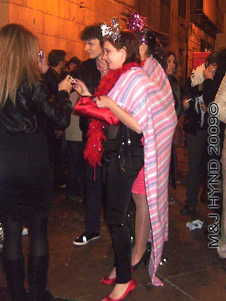 spain downtown Alicante, fiesta nochevieja New Years Eve, revellers party dress, pink shawl, feather-boa