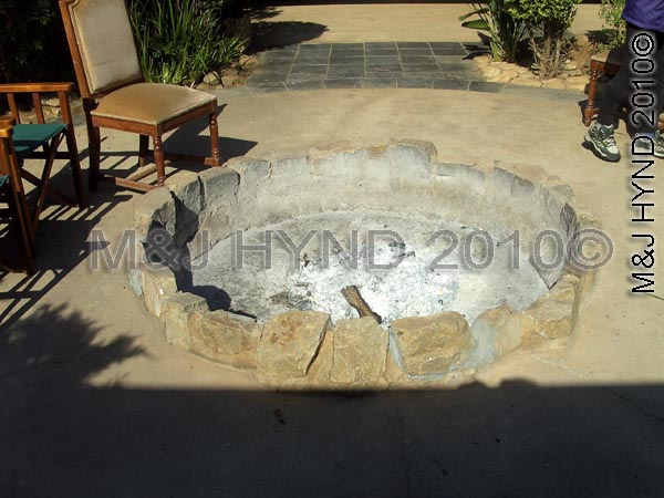 shamwari: Shamwari Game Reserve, Eastern Cape, South Africa, shallow firepit, rock surroud, seats, woodfire burn, logs