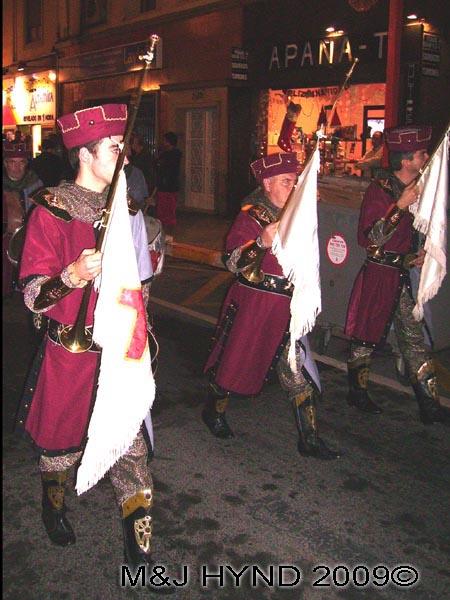 purple flag-bearers: Spain Alicante, Los Reyes Magos Three Kings' Fiesta Spanish Epiphany Christmas season, marching holiday parade, flag bearers in medieval attire