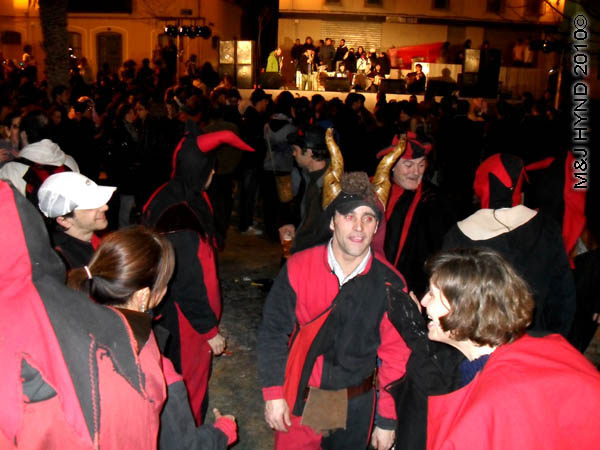 blk/red with horns: spain Alicante Carnival Fiesta, Costa Blanca, darkened plaza, bright-lit stage, spectators dressed in black and red, dance court jester with gold horns