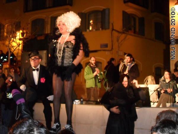 cross dresser: spain Alicante Carnival Fiesta, Costa Blanca, darkened plaza, bright-lit stage, spectators dressed in black and red, black man dance, skimpily dressed singer in drag, musicians
