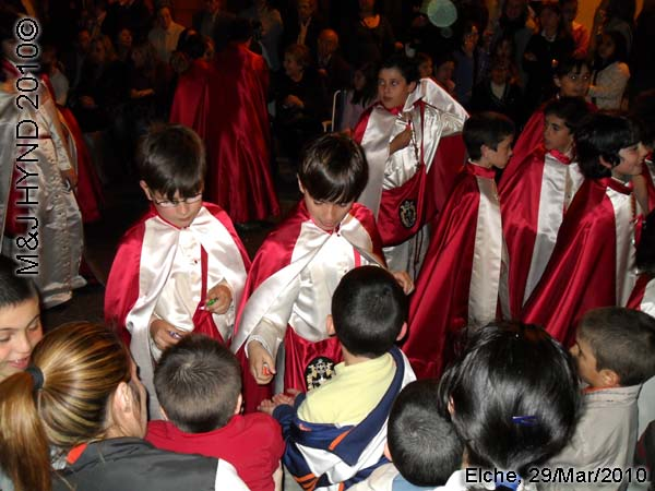 spain elche, Brotherhood long capes, procession giving sweets to spectators, near Townhall, crowded street parade