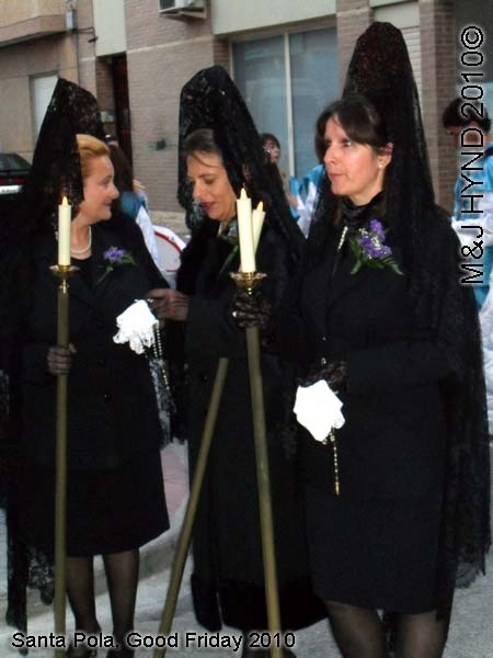 spain Santa Pola, Semana Santa Holy Week, Good Friday procession, black lace-mantilla dressed ladies carry candle on poles