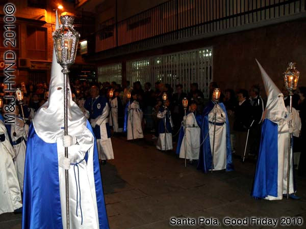 spain Santa Pola, Semana Santa Holy Week, Good Friday procession, Brotherhood long pointed white hoods, long capes carry lamps on poles