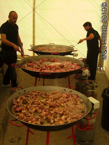 paella cooking: spain perleta maitino St Vicente de Ferrer Fiesta, giant paella, searing the meat - sausages chorizos, Arroz con Costra