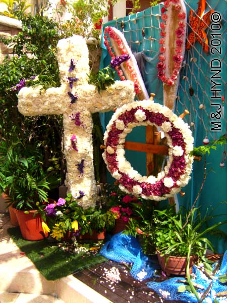 cross+wreath: spain, Alicante Santa Cruz Fiesta, festive buntings, white fresh flowers decorated Crosses white purple wreath, little pink roses paddles, aquatic scene starfish fishing nets