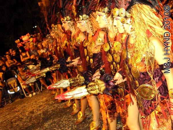 parade – red+gold: spain Santa Pola Annual Fiesta, procession Moorish warrior women, carry mock spears, confetti
