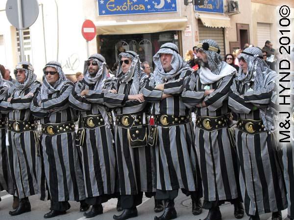 grey+black striped: spain Santa Pola Annual Fiesta, Moorish men, costumed grey+black striped arm-in-arm procession