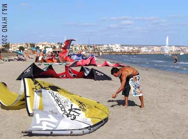 Spain Santa Pola, kite-surfers getting their stuff ready, town in background