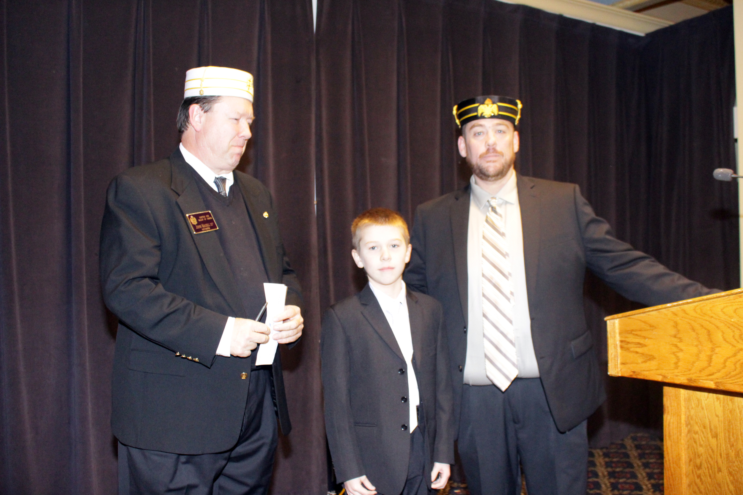 Mike O'Donnell, 32°, assisted by son Kody, presents a check for $5,000 to John Maxell, 33°, at the November 16 Lodge dinner.