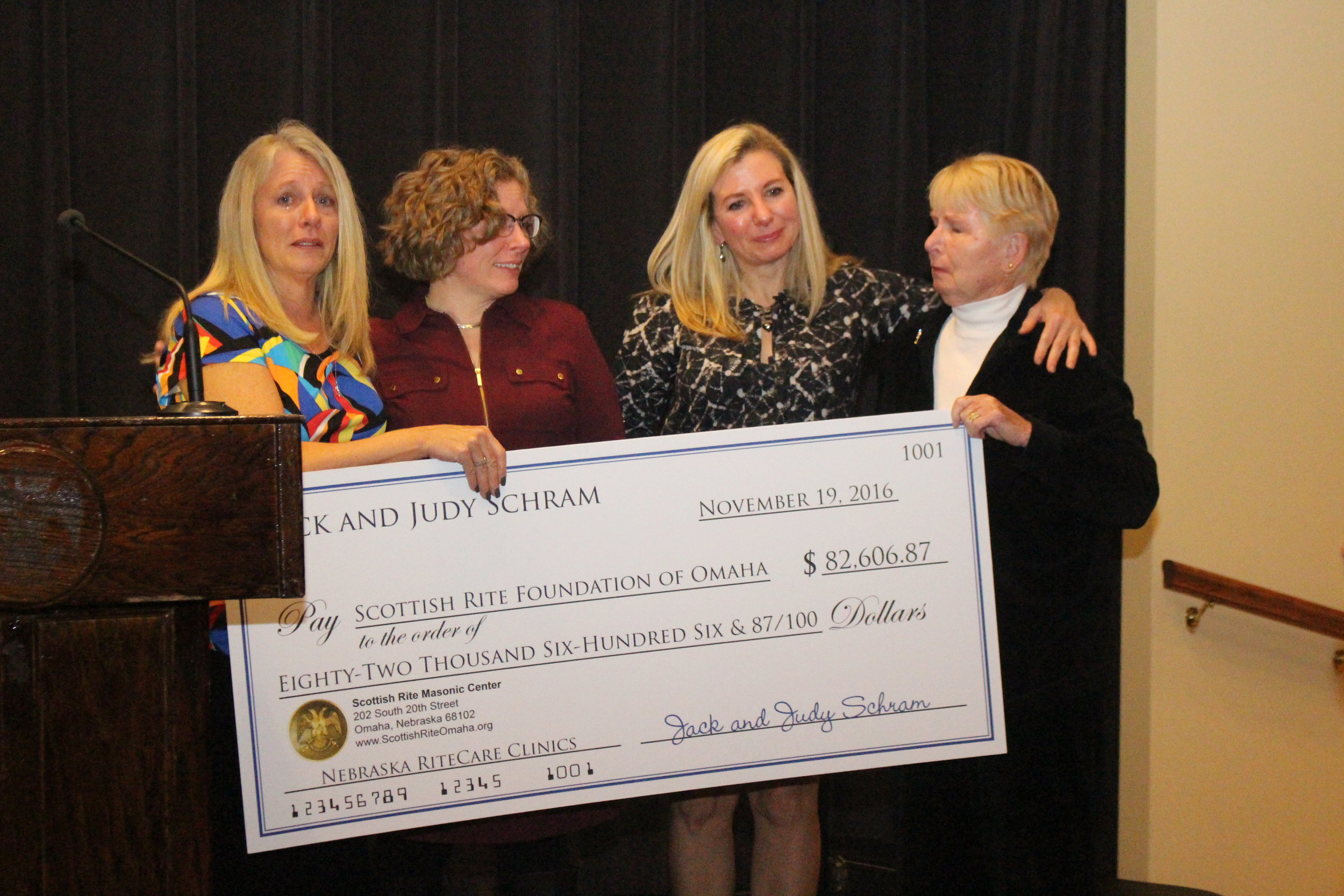 Judy Schram and daughters presenting a check to the Omaha Foundation for RiteCare at the Reunion Banquet Saturday evening.
