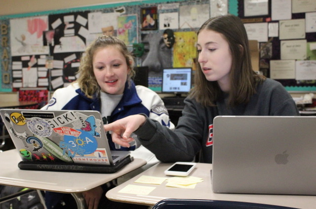 Alyssa Freyman (rt.) helps a fellow student with designing a featured image on Photoshop. Photo taken by Sadie Rawlings