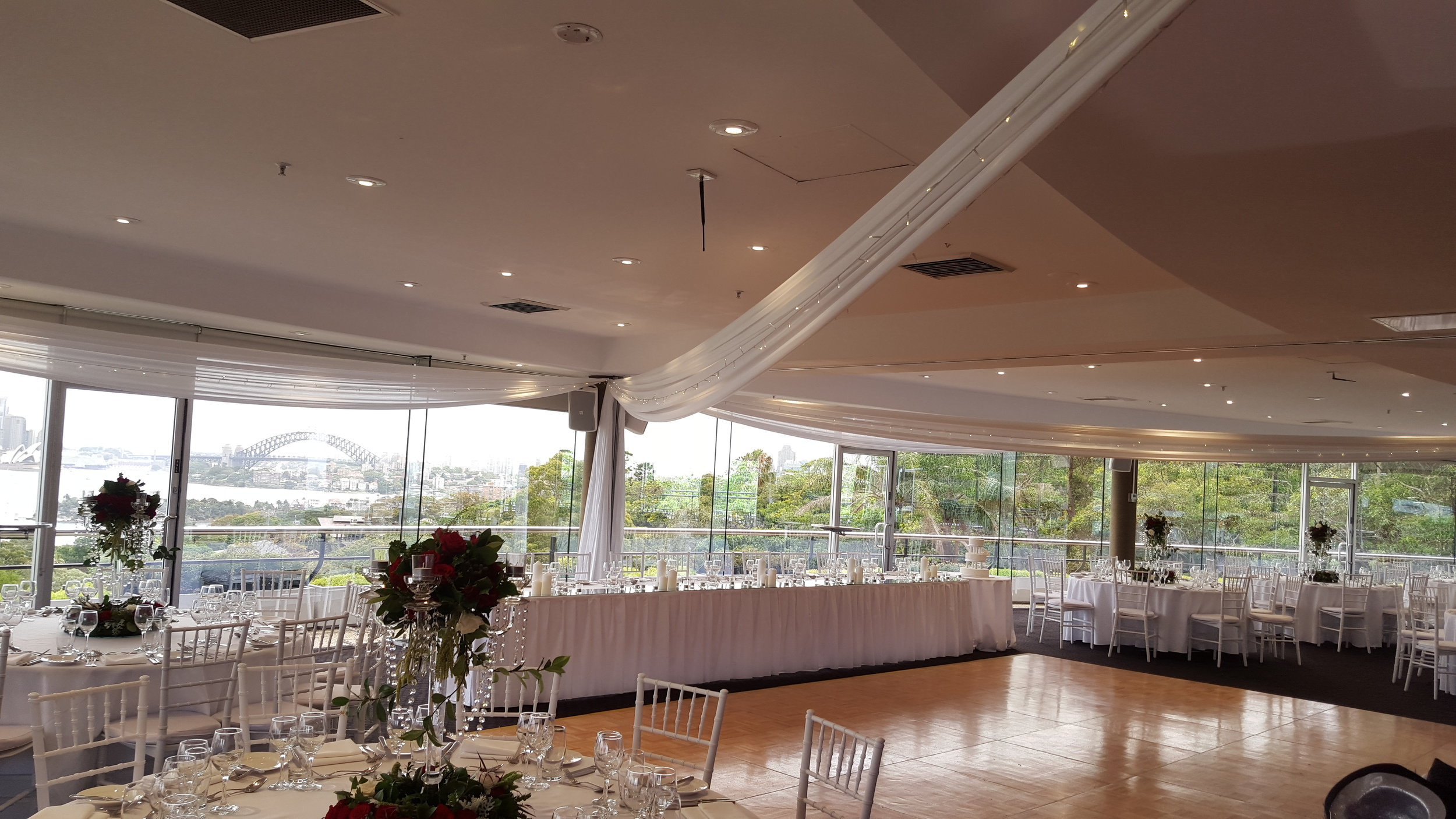 White silk drapes, fairy lights, centrepieces & bridal table styling by Fairytale Events - Taronga Centre