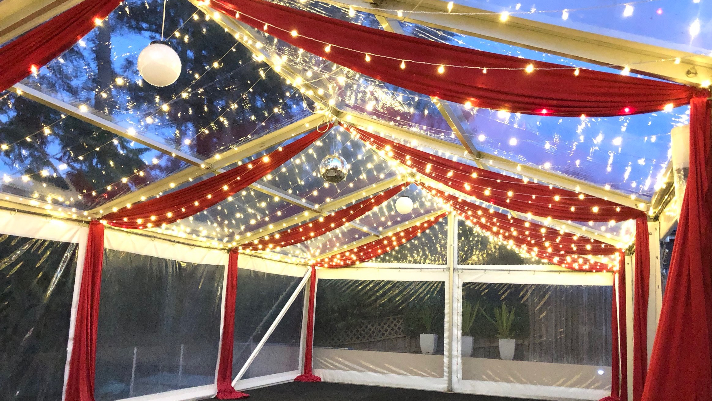 Red silk drapes with fairy lights by Fairytale Events - Private marquee