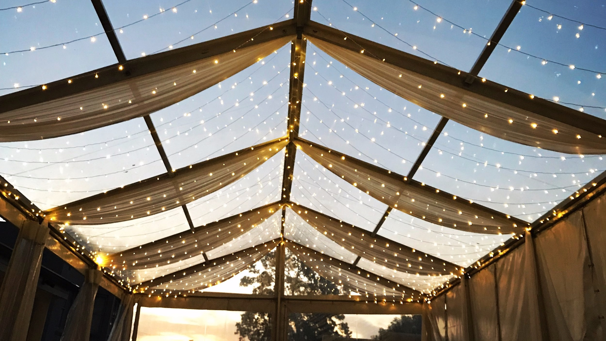 White silk drapes with fairy lights by Fairytale Events - Private marquee