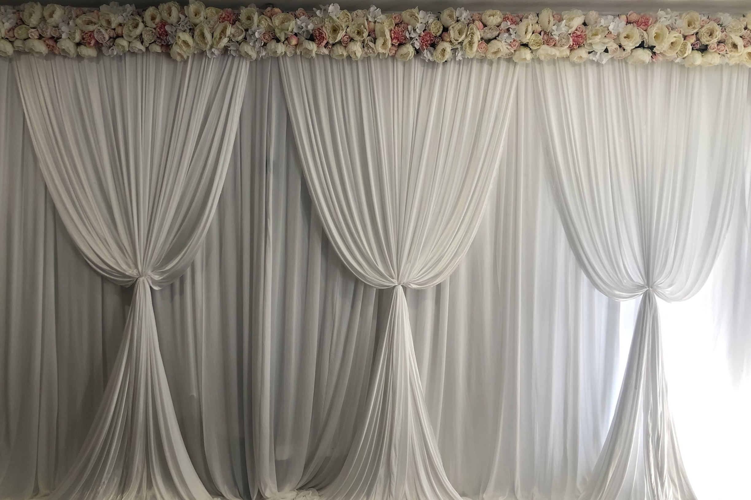 White scalloped backdrop with floral top