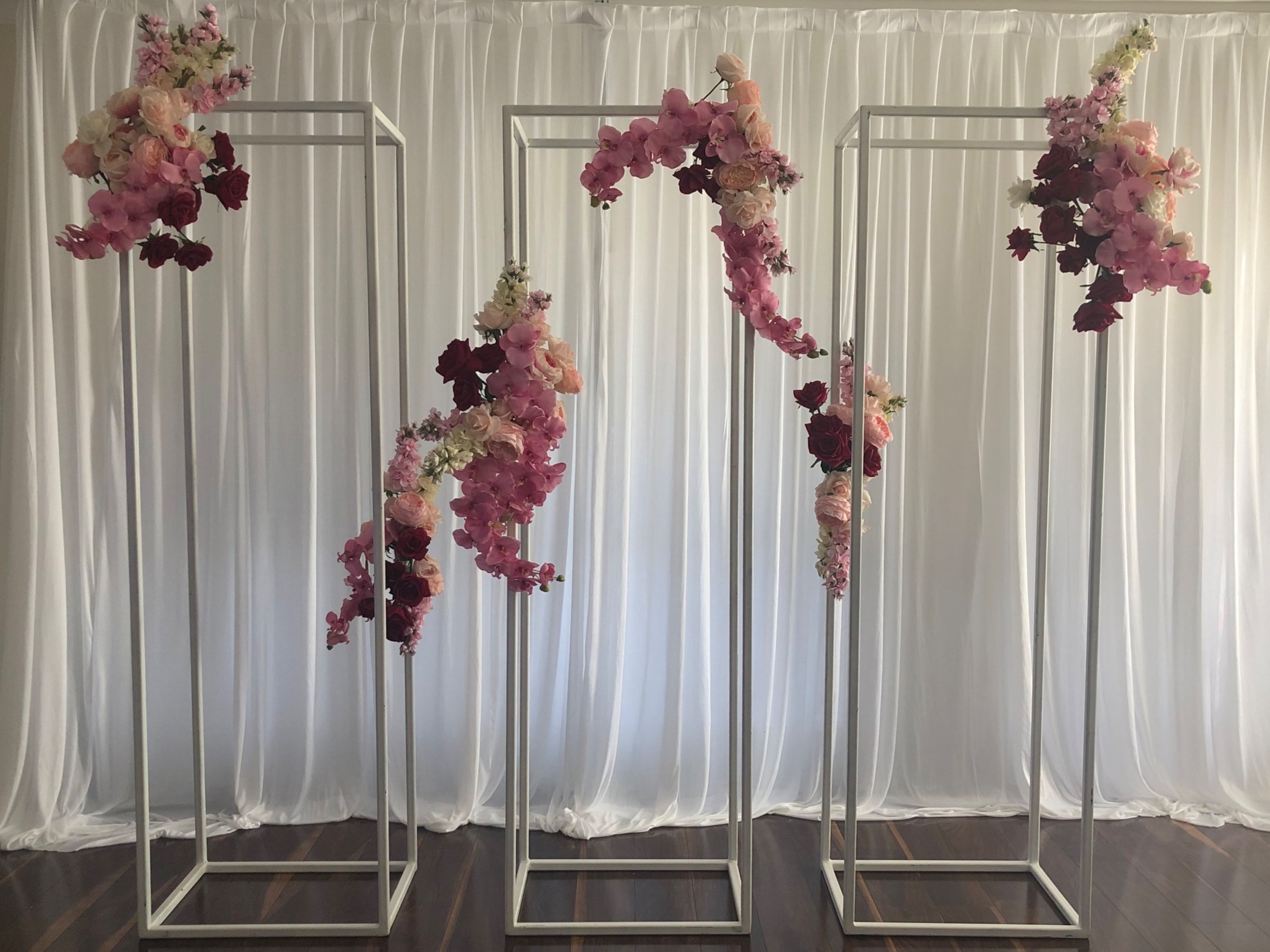 White rectangle frame display stand shown with plain white backdrop and our Lola artificial floral