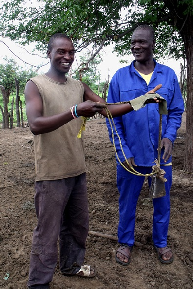 A Happy Cattle Owner proudly displays our cattle tracker unit with our Project Assistant Chris (left)