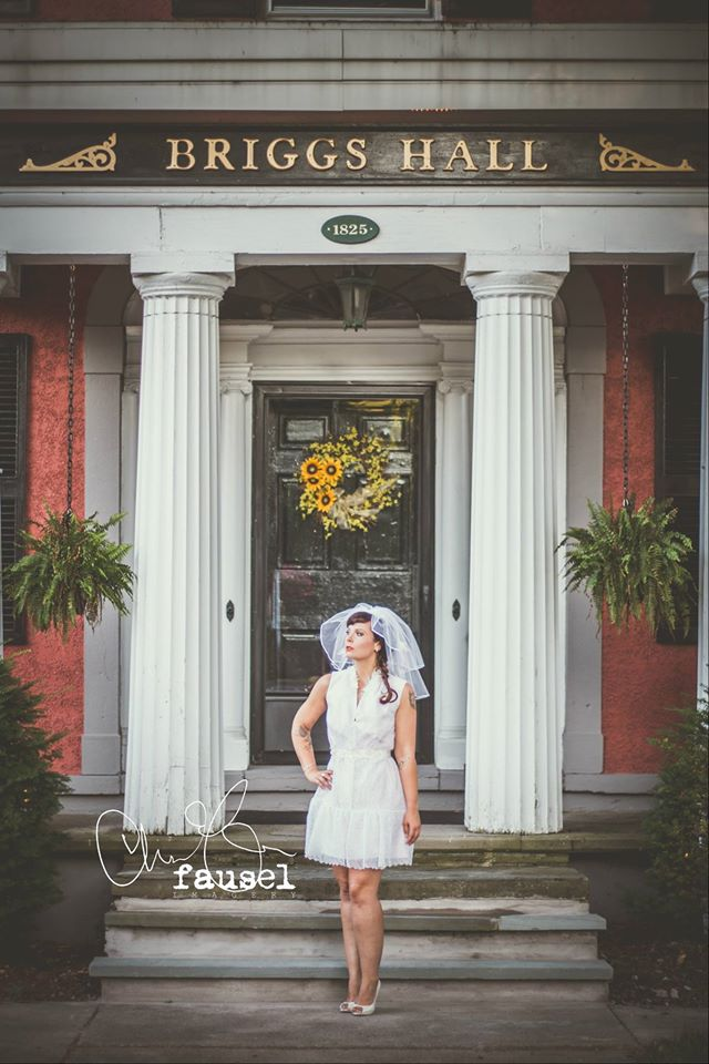 Model Mariah wears a Gee June Little White Dress, Bridal Belt, and Civic Veil in front of Briggs Hall in Homer, NY.