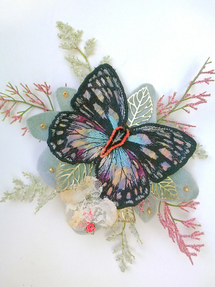 To hide the elastic of the wreath's head band we made this velvet lamb's ear and butterfly comb. The butterfly was embroidered on top of feathers in lightened shades of yellow, blue and magenta.