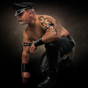 Man in leather pants and studded cuffs, kneeling on one knee.