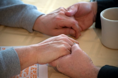 Two sets of male hands holding each other.