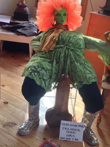Sitting scarecrow with a pink wig and a blue dress
