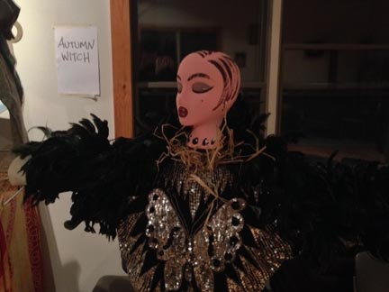 Standing scarcrow with painted hair, a sparkling dress and a black feather boa.