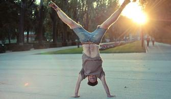Man doing handstand on pavement with sun setting in background