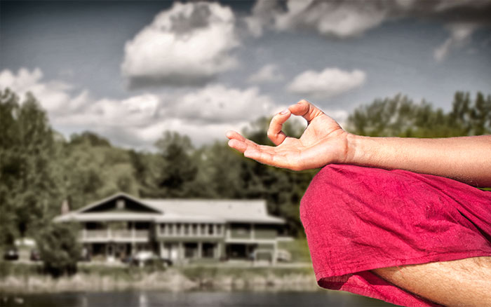 Guest House in background; knee and forearm of person practicing seated meditation