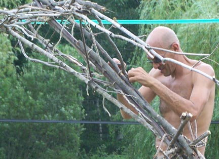 Man tying sticks together to make a sculpture