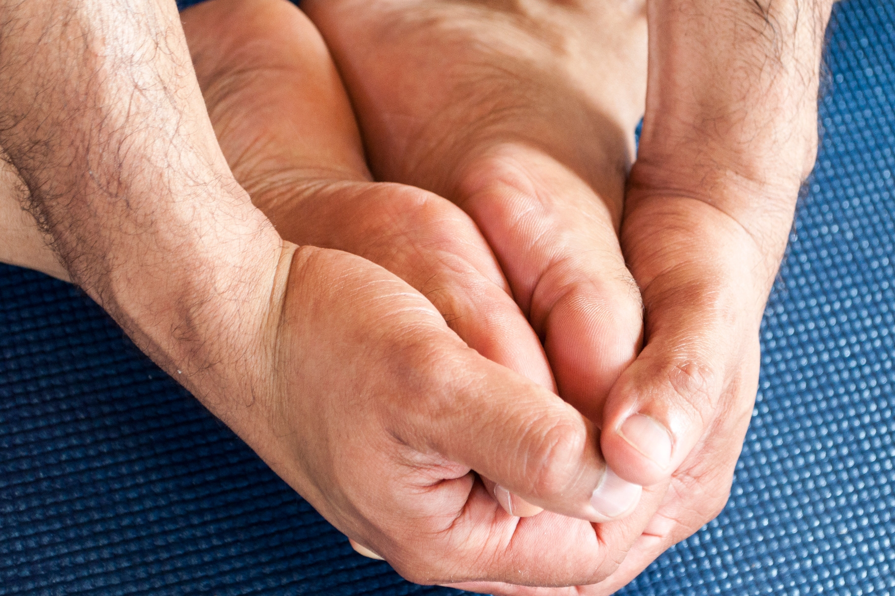 Two hands clasped around two feet together