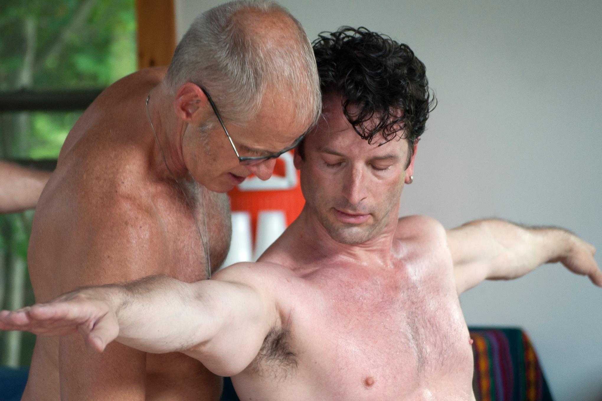 Two men practicing partnered yoga