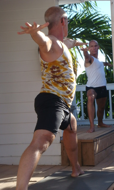 Two men outdoors, facing each other, doing yoga
