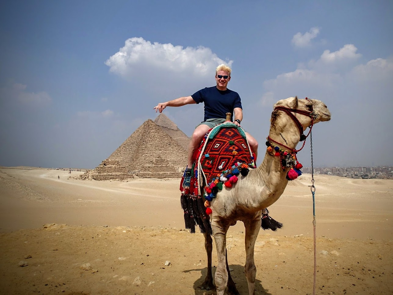 Christian riding a camel and geeking out at the Great Pyramid of Giza in Egypt