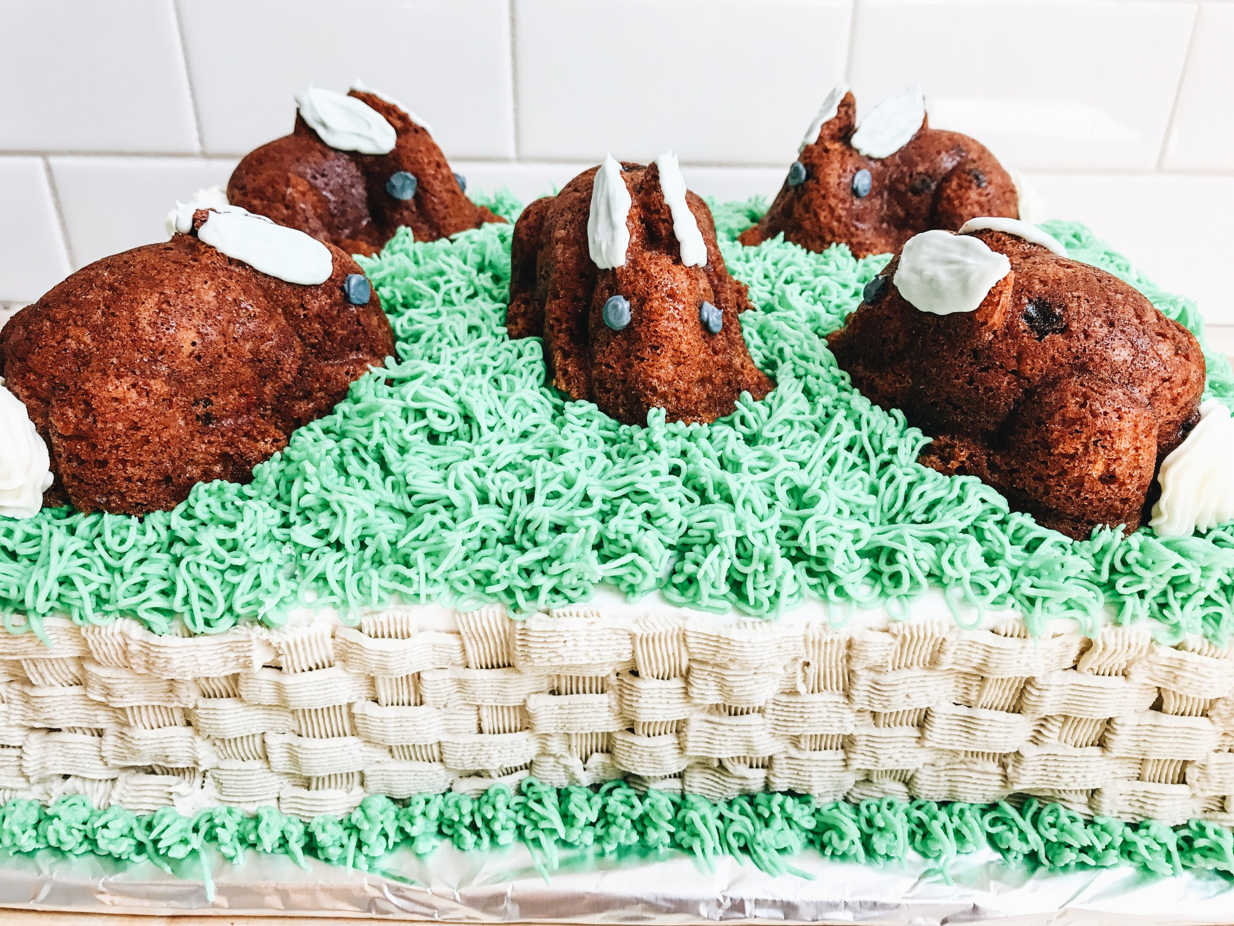 Easter Cake with bunnies on top of it. Bunnies hopping around in the grass.