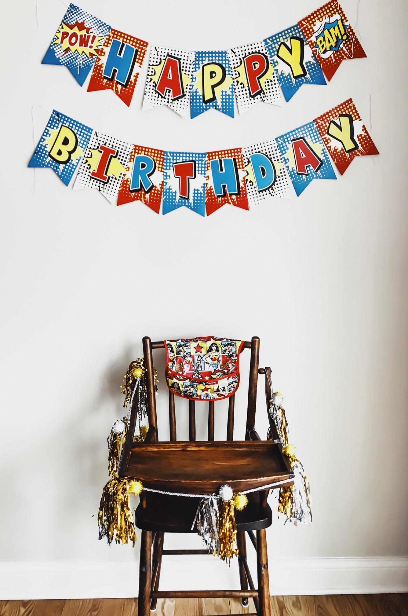 Wonder Woman High Chair Decor. Superhero birthday day party. Wonder Woman Onesie. Wonder Woman Superhero Birthday Party Theme Ideas. How to Plan a Wonder Woman Themed 1st Birthday Party. #sponsored #wonder#woman #birthday #party #decor