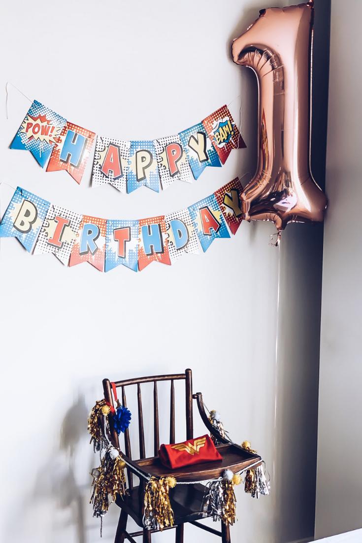 Wonder Woman High Chair Decor. Superhero birthday day party ideas. Wonder Woman Onesie for 1st Birthday Party. Wonder Woman Superhero Birthday Party Theme Ideas. How to Plan a Wonder Woman Themed 1st Birthday Party. #sponsored #wonder#woman #birthday #party #decor