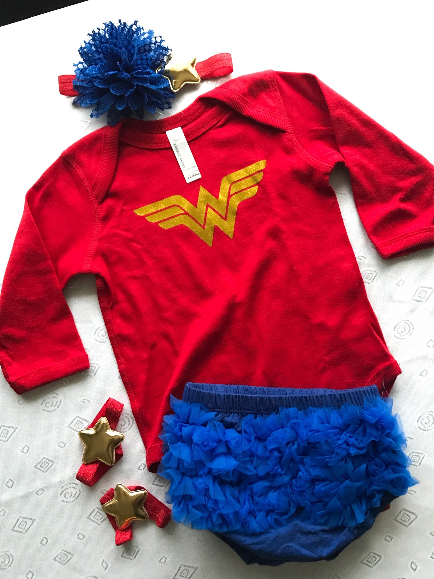 Wonder Woman Outfit For A Baby. Wonder Woman Onesie. Wonder Woman Superhero Birthday Party Theme Ideas. How to Plan a Wonder Woman Themed 1st Birthday Party. #sponsored #wonder#woman #birthday #party #decor