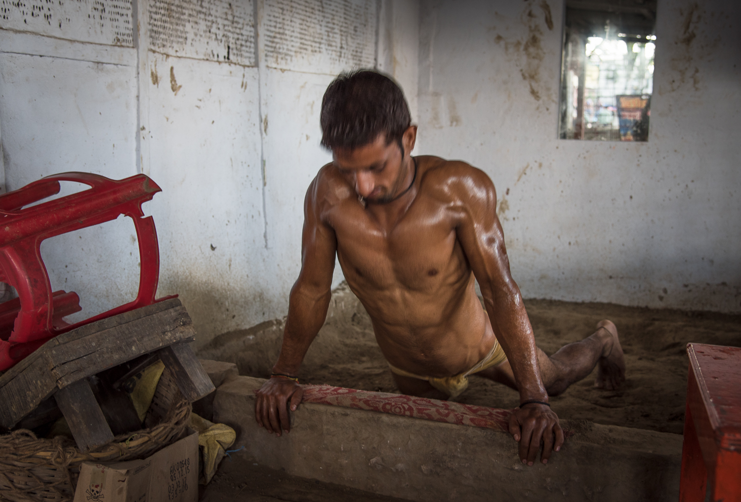 "© Ayash Basu. 20 year old Suraj Kant Tiwari (Jwala Kant's son) is an emerging wrestler. While his father is away at Gorakhpur to attend to family matters, he oversees the daily operations of the akhara. Most young athletes today, look for the means and access to modern gyms and equipment for training. The results are quicker, as more advanced training is possible. ""But your body looses flexibility and agility, which are extremely important for a wrestler. This is hard work done in very basic environments but we'd rather stick to this to preserve longevity,"" argues Suraj Kant as he does 3 sets of 50 push ups each following his prayers. Suraj has participated in and won many local tournaments, once inches away from wrestling in the national championships until he did not make it. ""Winning tournaments is good as it gives us exposure and recognition, but kushti is a way of life for us, has been in my family for many generations and we must work harder to keep its survival. In this day and age, nobody cares about kushti and pehlwans."""