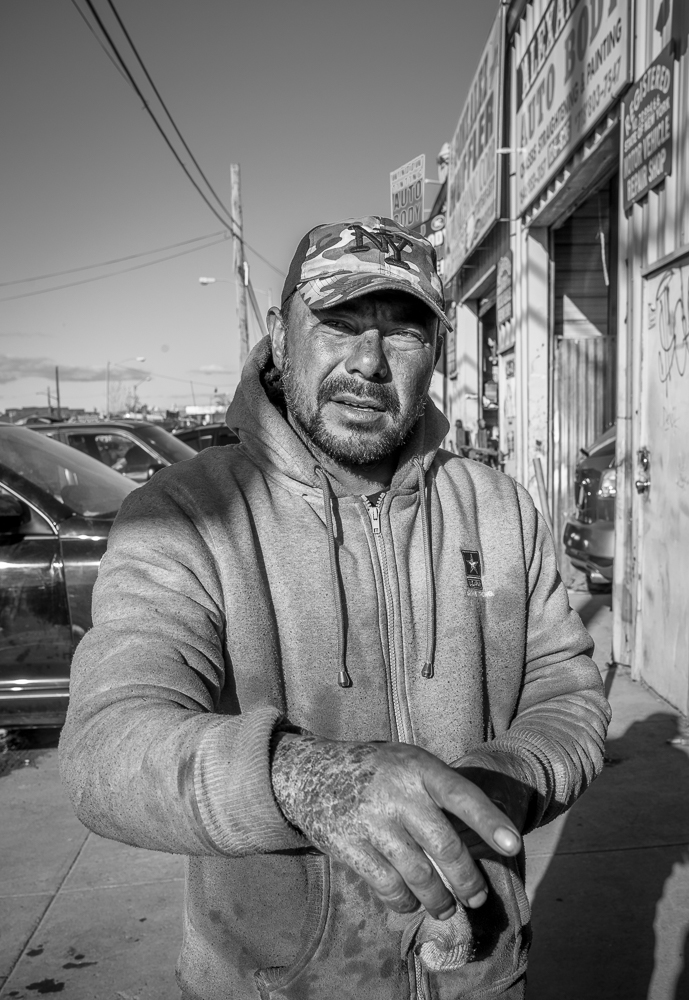 Oscar points to parts of Willets Point where some redevelopment has already taken place. His hand was badly burnt in a recent chemicals accident at the shop.