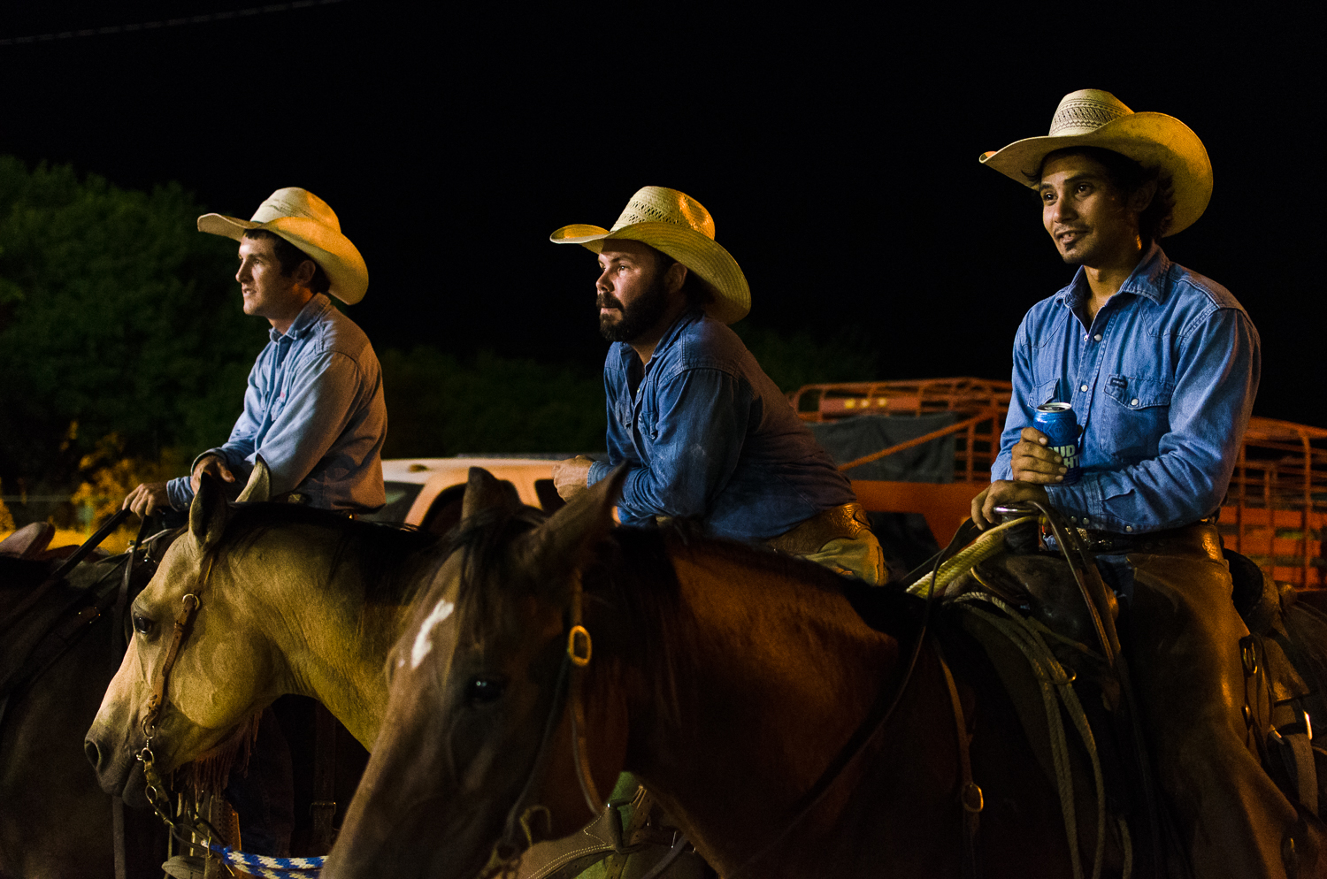 © Ayash Basu. Cowboys from one ranch watch intently as another outfit performs. They are up next and get ready by the gates, Bud Light and Coors get consumed by the gallons before and after each event, and there are seven to eight in one night. Bandera 2017.