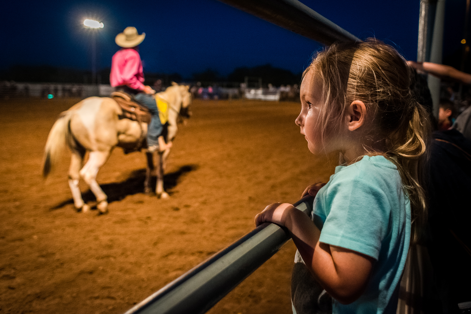 © Ayash Basu. Cowboy families come out in full swing to support and cheer for them. This young girl's Dad was one of the riders in the arena, and she couldn't take her eyes off him. Johnson City 2017.