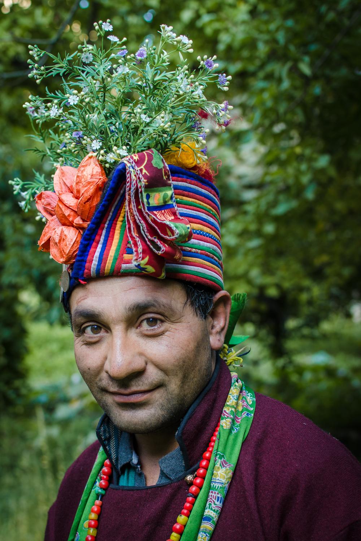 © Ayash Basu. Brokpa men wear traditional maroon gowns with cummerbunds and often use the flowery headgear just like women.