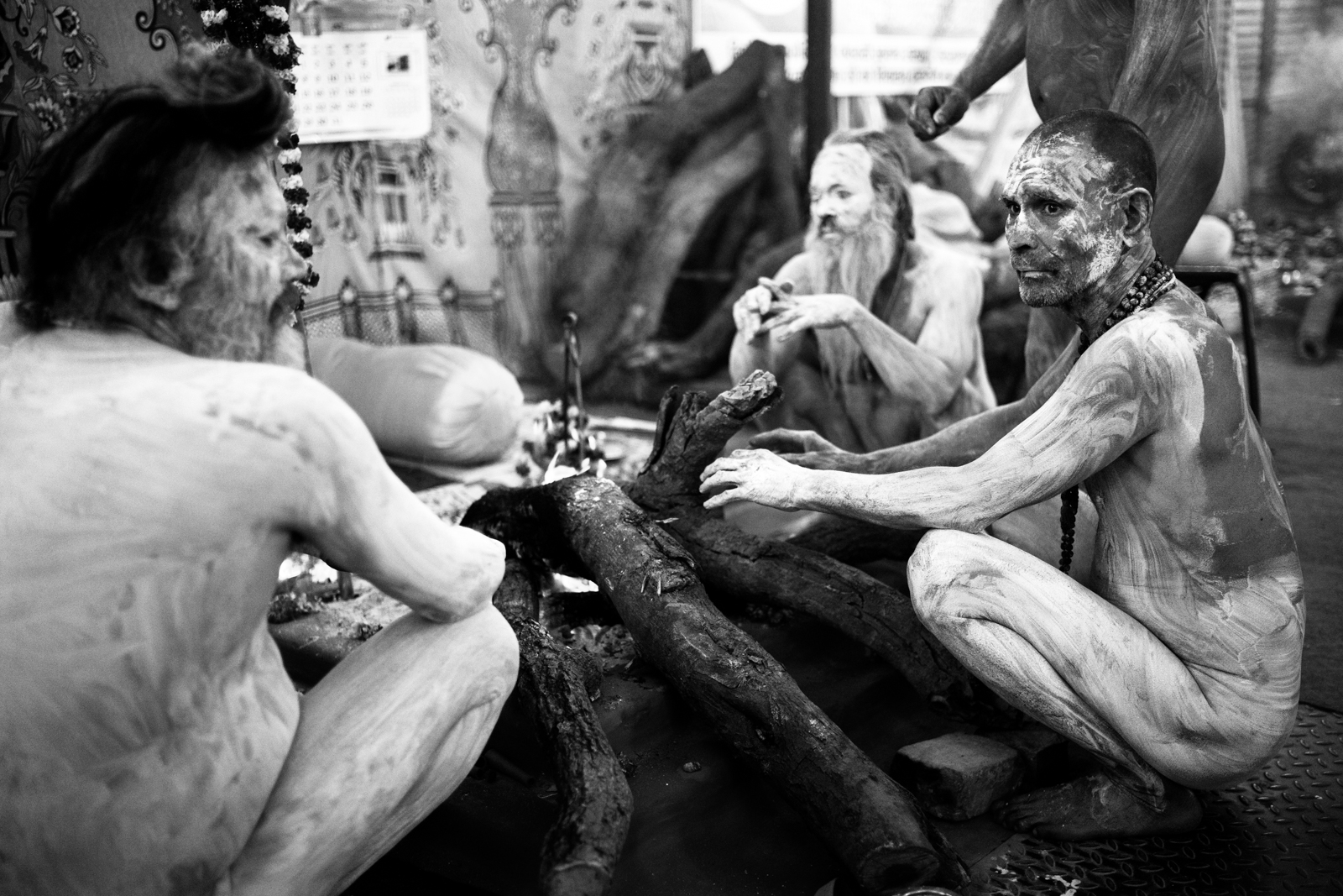 © Ayash Basu. Ash-smeared Naga sadhus warming up for morning prayers at 3 a.m. Historically, Nagas have been fearsome warriors, defending key Hindu temples and cities from Mughal attacks.